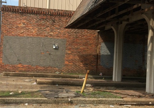 Graffiti has been covered up by gray paint on an abandoned bank on Broad Street (Della Hasselle, Mid-City Messenger).