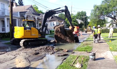City workers remove a section of pavement from Pine Street in May 2015 to repair a broken water main underneath it. (Robert Morris, UptownMessenger.com)