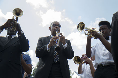 """Dr. Michael White, center, leads a band in """"When the Saints Go Marching In"""" after the wreath laying concluded. White kicked off the ceremony with a rendition of  """"Amazing Grace."""" (Zach Brien, MidCityMessenger.com)"""