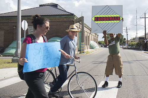 "Virginia Brisley, left, and Tyrone Smith, right, escort a cyclist on the Lafitte greenway as he crosses north broad street. Brisley and Smith were part of the ""Safe-Tea on the Greenway"" event on Friday which promoted cyclist, pedestrian and auto safety at the major cross streets along the Lafitte greenway. (Zach Brien, MidCityMessenger.com)"