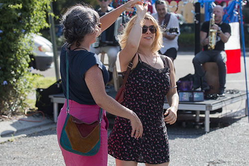 Caroline Helm, left, and Kara St. Clair, right, dance to Harmonouche at the annual Bastille Day festival off of Esplanade avenue. (Zach Brien, MidCityMessenger.com)