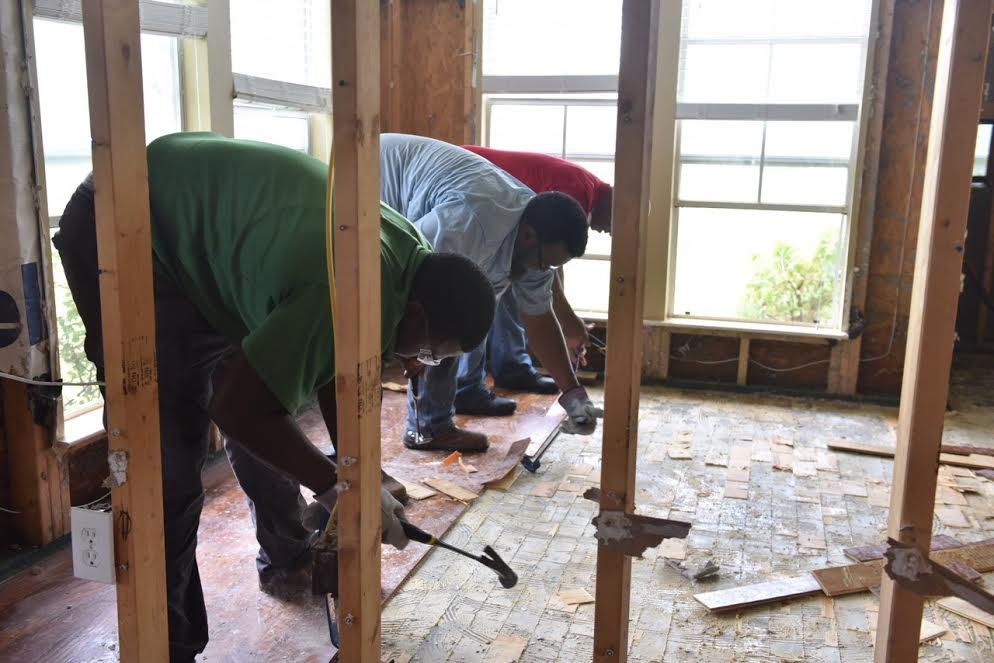 From left: Delgado Carpentry Instructor Tim Davis, student Alex Johnson and Instructor Kenneth Williams demo floors in a flooded home (photo courtesy of Delgado Community College).