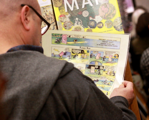 "A member of the audience reads a full-page, full-color ""Krazy Kat"" comic strip. (Robert Morris, UptownMessenger.com)"