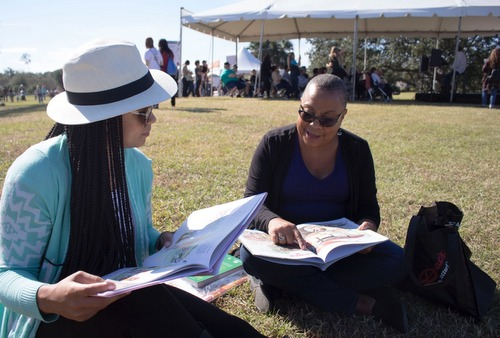 Angel Dabon and Daryl Dabon Jarvis, both of New Orleans, read beside the Big Lake at City Park. Thousands came to The New Orleans Book Festival on Nov. 12, 2016. (Photo by Alliciyia George)