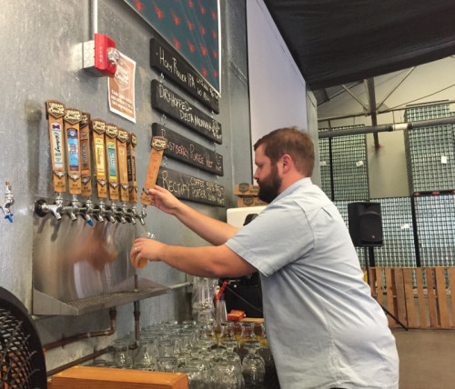 Kyle Huling, the vice president of Urban South, serves beers to a line of customers. On Friday Nov. 11, Urban South Brewery celebrated the expansion of their brewery after being in business for just 7 months (Photo by Dannielle Garcia).