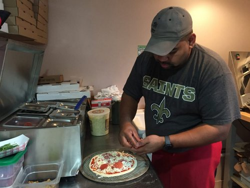 Oscar Garcia, Uptown Slice Pizza and Wings manager and chef, makes a pizza in the side kitchen. The restaurant opened Dec. 6.  (Photo by Haley Pegg)