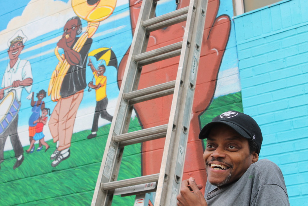Keith Duncan, lead artist, explains to dozens of volunteers how to coat the Lemann Pool murals with varnish over the MLK Weekend. (Claire Byun/cbyun@nolamessenger.com)